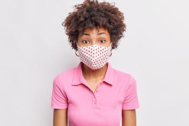 La donna sorpresa con i capelli ricci indossa una maschera usa e getta durante la quarantena e l'epidemia di coronavirus si preoccupa della salute indossa una maglietta rosa casual isolata sul muro bianco