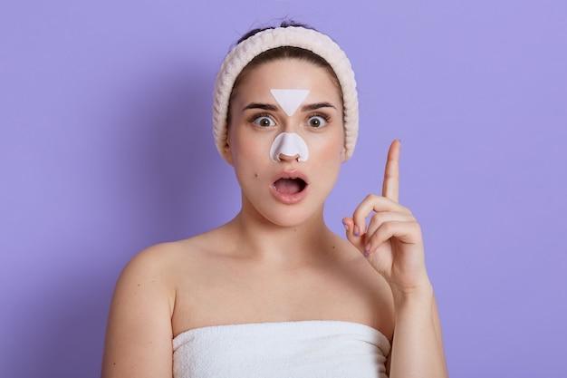 코와 이마에 얼굴 마스크를 쓰고 놀란 여자는 미용 절차, 충격적인 표정, 검지 손가락으로 가리키고 수건을 감싸고 라일락 벽 위에 고립 된 헤어 밴드를 착용합니다.