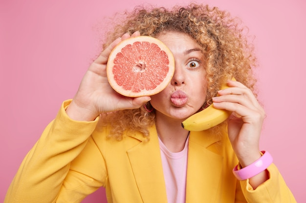 Surprised woman with folded lips curly hair keeps half of grapefruit over eye fresh banana near ear pretends telephone talk has curly hair dressed in fashionable yellow jacket. female holds ripe fruit