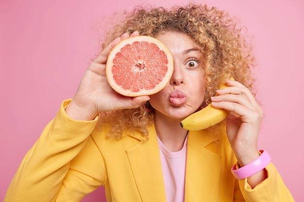 접힌 입술 곱슬 머리를 가진 놀란 여자는 귀 근처의 신선한 바나나 눈 위에 자몽의 절반을 유지합니다. 전화 통화는 세련된 노란색 재킷을 입은 곱슬 머리를 가지고 있습니다. 여성 보유 익은 과일