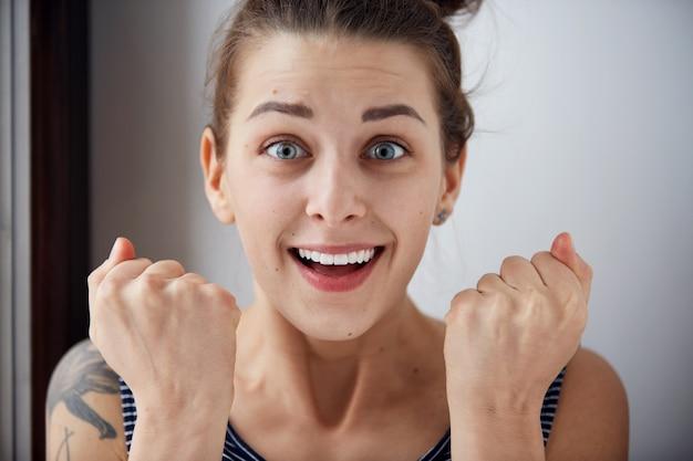 Удивленная женщина с поднятыми руками, пораженная или шокированная неожиданными новостями