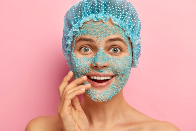 Surprised woman with happy look, covers face with blue granules of sea salt, peels from pores and acnes, wears protective headgear during taking bath