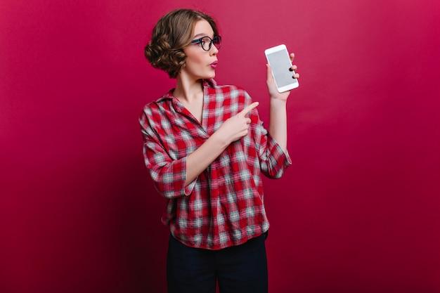 変な表情でスマートフォンを見て小さな腕のタトゥーで驚いた女性。クラレットの壁にセルでポーズをとってカジュアルな服装で巻き毛の茶色の髪の少女の屋内写真。