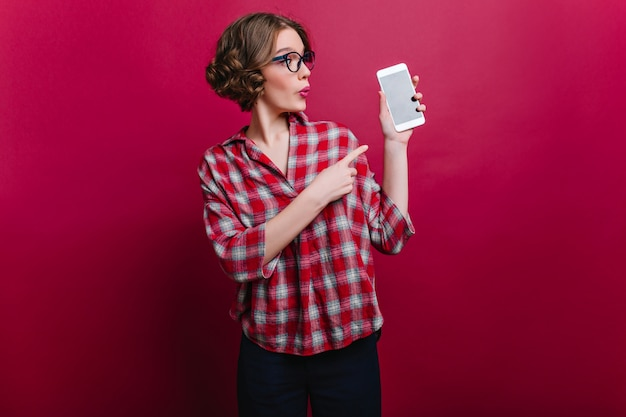Surprised woman with little arm tattoo looking at smartphone with funny face expression. indoor photo of curly brown-haired girl in casual attire posing with cell on claret wall.