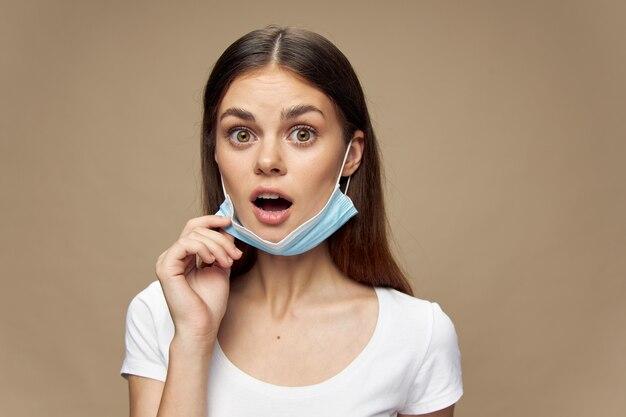 ベージュに白いtシャツの医療マスクを持つ驚く女性