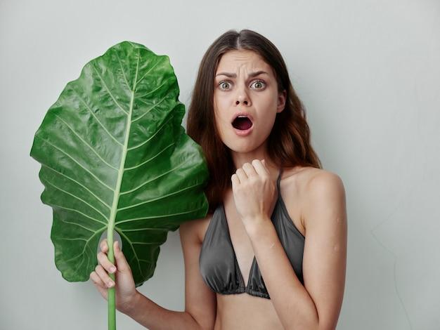 大きな緑の葉の孤立した背景を保持している水着で口を開けて驚いた女性