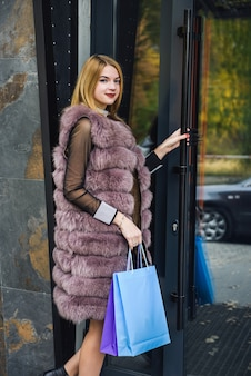 Surprised woman with shopping bag in fur coat posing outdoors