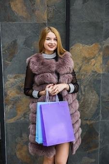 屋外でポーズをとる毛皮のコートで買い物袋を持って驚いた女性