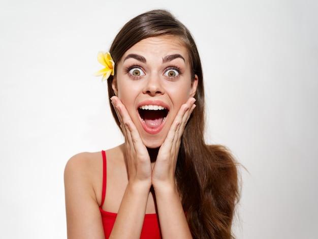 彼女の髪に黄色い花を持つ驚いた女性は彼女の口を大きく開いた喜びの感情