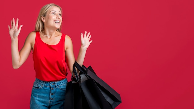Surprised woman woman holding shopping bags with copy space