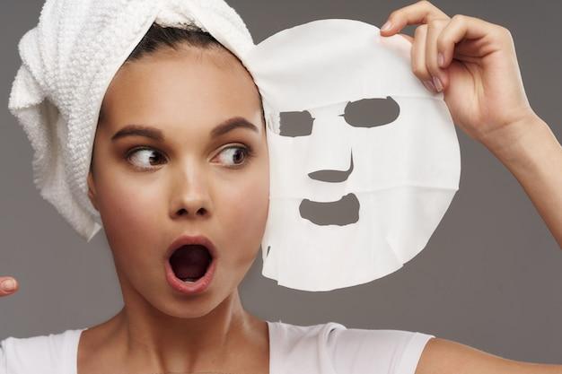 놀란 여성이 마스크를 검은 점에 대해 검사합니다.