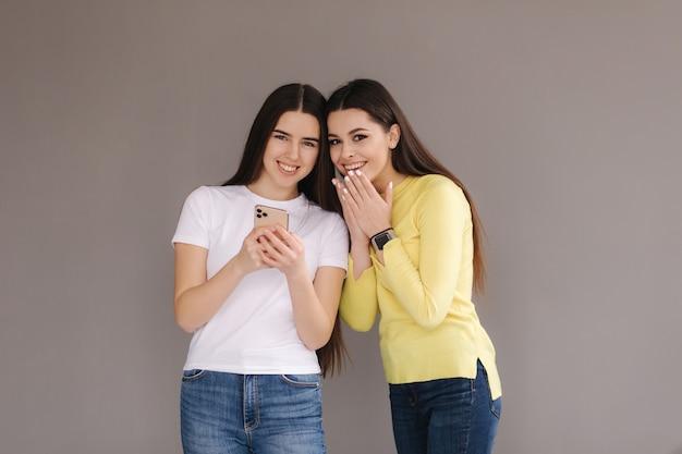 驚いた女性は電話を見て、灰色のスタジオで魅力的な若い女性を手で口を閉じます