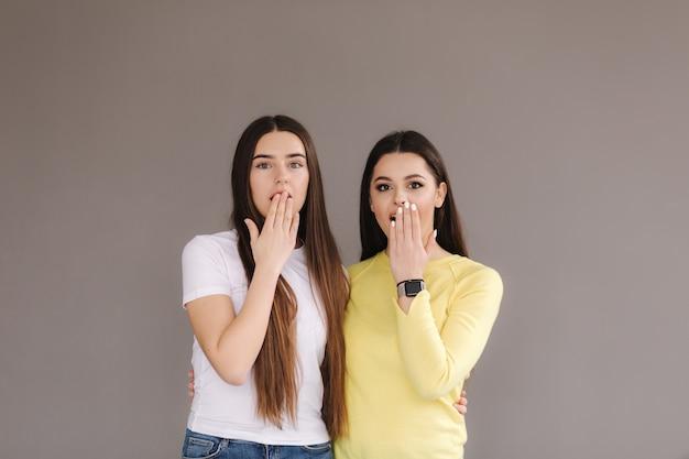 驚いた女性はカメラをのぞき、灰色のスタジオで魅力的な若い女性を手で口を閉じます