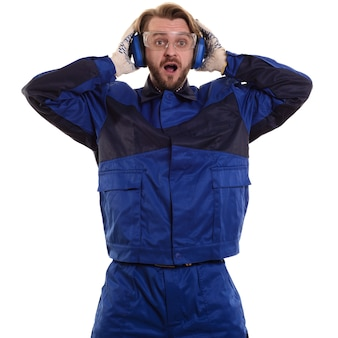 Surprised worker in glasses is standing with his mouth holding his safety headphones