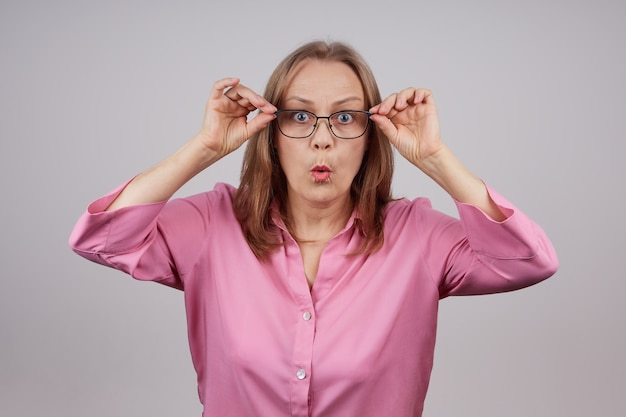 불 룩 한 눈으로 카메라를보고 안경 놀라게, 걱정 성숙한 비즈니스 여자. 회색 배경에 고립 된 사진입니다.