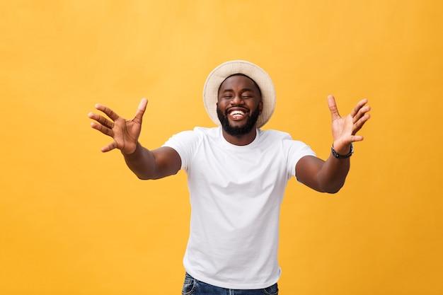 Удивленный молодой афроамериканец в повседневной серой футболке, потрясенный взглядом смотрящий в камеру, выражающий удивление и шок.