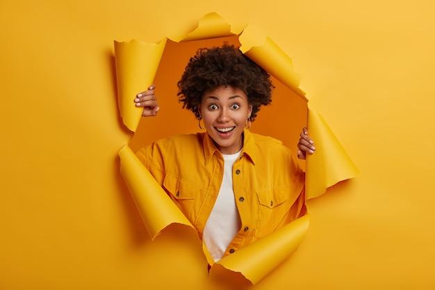 놀란 젊은 아프리카 계 미국인 여자는 세련된 옷을 입고 찢어진 종이 구멍에 서, 쾌활한 표정을 흥분했다