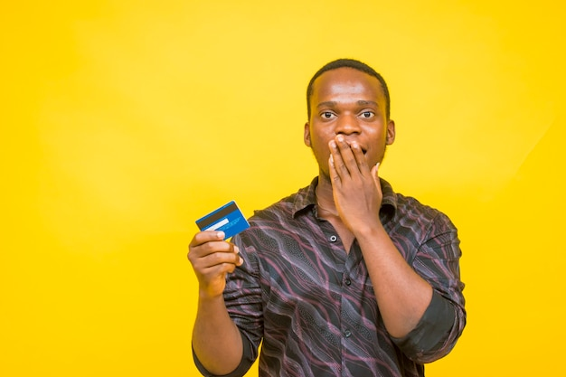 A surprised young african man holding up a credit card with his right hand.