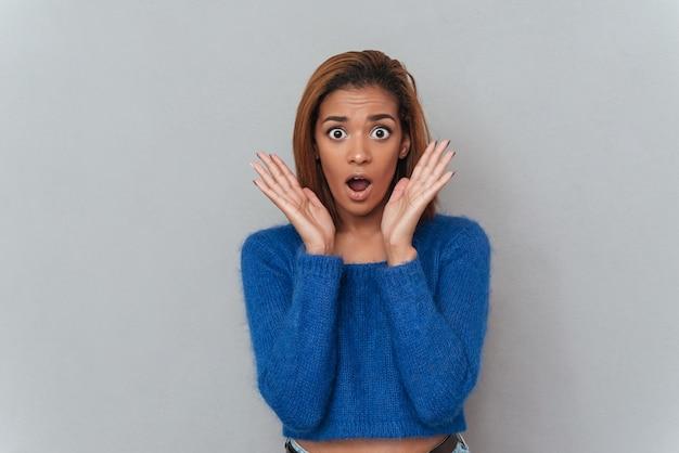 얼굴 근처에 손을 잡고 입을 벌리고 있는 스웨터를 입은 젊은 아프리카 여성