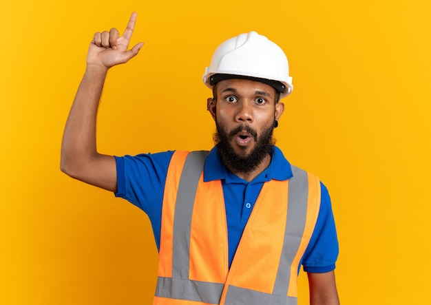 Surprised young afro-american builder man in uniform with safety helmet pointing up isolated on orange background with copy space
