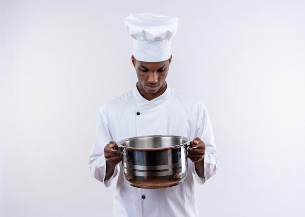 シェフの制服を着た驚いた若いアフリカ系アメリカ人の料理人は、コピースペースと孤立した白い背景の上の鍋を見て