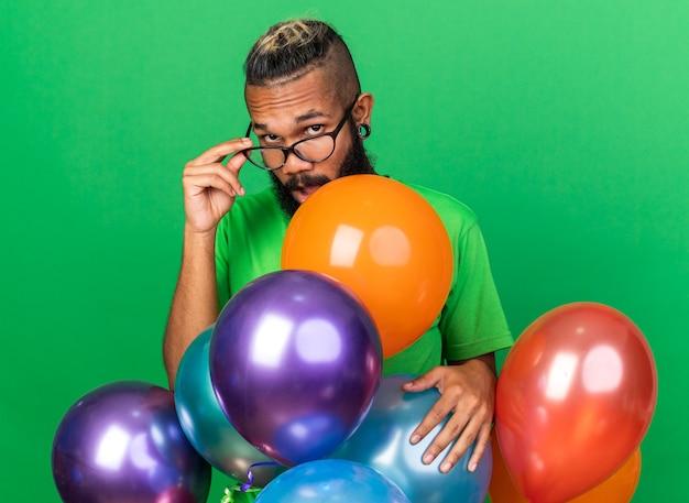 緑の壁に隔離された風船の後ろに立っている緑のtシャツと眼鏡を身に着けている驚いた若いアフリカ系アメリカ人の男