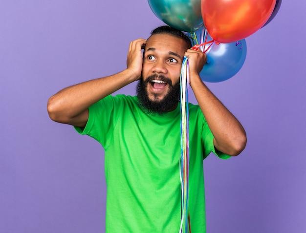 풍선을 들고 녹색 티셔츠를 입고 놀란 젊은 아프리카계 미국인 남자가 머리를 움켜잡았다