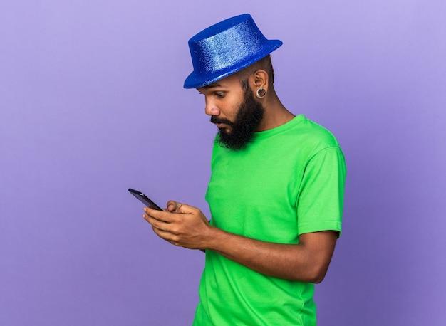 Удивленный молодой афро-американский парень в партийной шляпе, держащий и смотрящий на телефон, изолированный на синей стене