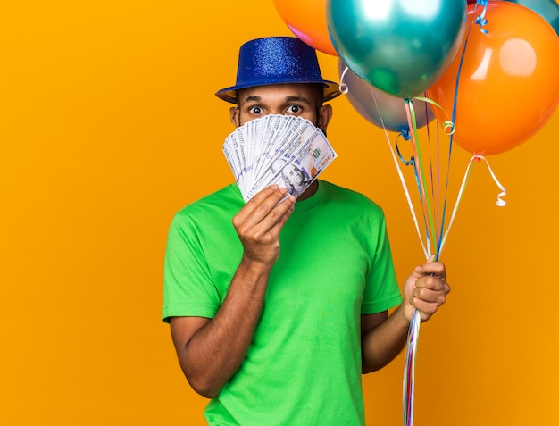 Surprised young afro-american guy wearing party hat holding balloons and covered face with cash isolated on orange wall