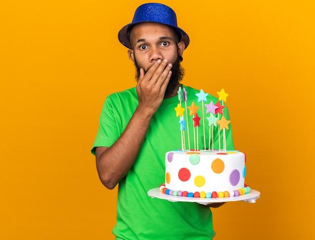 Sorpreso giovane ragazzo afro-americano che indossa un cappello da festa tenendo la torta ricoperta di faccia con la mano isolata sul muro arancione