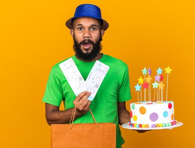 オレンジ色の壁に隔離されたチケットとギフトバッグとケーキを保持しているパーティーハットを身に着けている驚いた若いアフリカ系アメリカ人の男