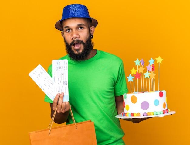 Sorpreso giovane afro-americano che indossa un cappello da festa con in mano una borsa regalo e una torta con biglietti isolati su una parete arancione