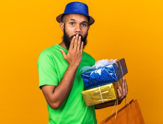 Sorpreso giovane ragazzo afroamericano che indossa un cappello da festa con scatole regalo con la bocca coperta dalla borsa con la mano
