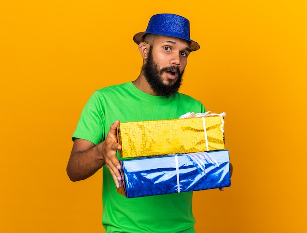 オレンジ色の壁に隔離されたギフトボックスを差し出すパーティーハットを身に着けている驚いた若いアフリカ系アメリカ人の男