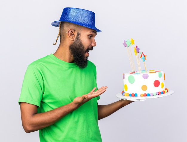 Surprised young afro-american guy wearing party hat holding and points at cake