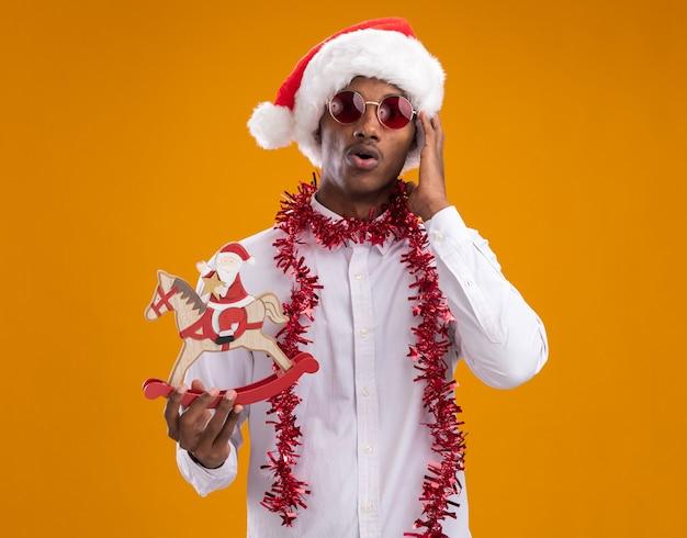 オレンジ色の背景で隔離の頭に触れるカメラを見てロッキングホースの置物にサンタを保持している首の周りに見掛け倒しの花輪とサンタの帽子と眼鏡を身に着けている驚いた若いアフリカ系アメリカ人の男