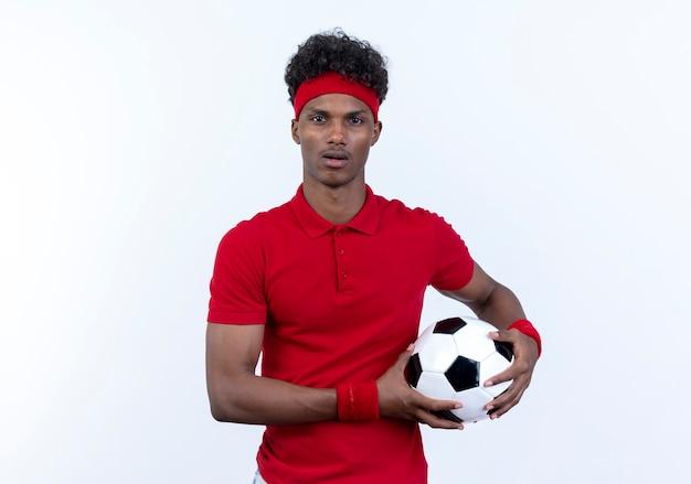 머리띠와 흰색에 고립 된 공을 들고 팔찌를 입고 놀란 젊은 아프리카 계 미국인 스포티 한 남자