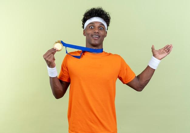 メダルとコピースペースで緑の背景に分離された手と横を指すヘッドバンドとリストバンドを身に着けている驚いた若いアフリカ系アメリカ人のスポーティな男