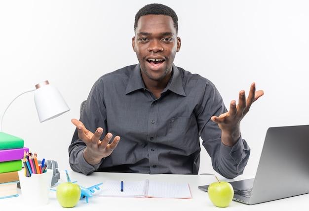 학교 도구를 들고 책상에 앉아 있는 놀란 젊은 아프리카계 미국인 학생