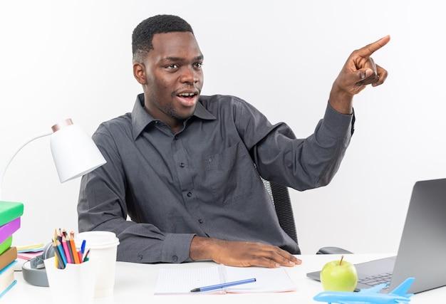 학교 도구로 책상에 앉아 옆을 보고 가리키는 놀란 젊은 아프리카계 미국인 학생