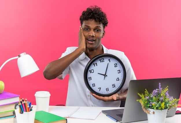 학교 도구를 들고 책상에 앉아 얼굴에 손을 대고 시계를 들고 놀란 젊은 아프리카계 미국인 학생