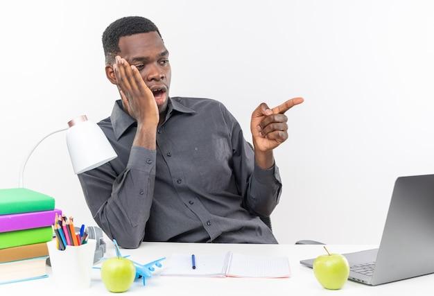 Sorpreso giovane studente afroamericano seduto alla scrivania con gli strumenti della scuola mettendo la mano sul viso guardando e indicando a lato