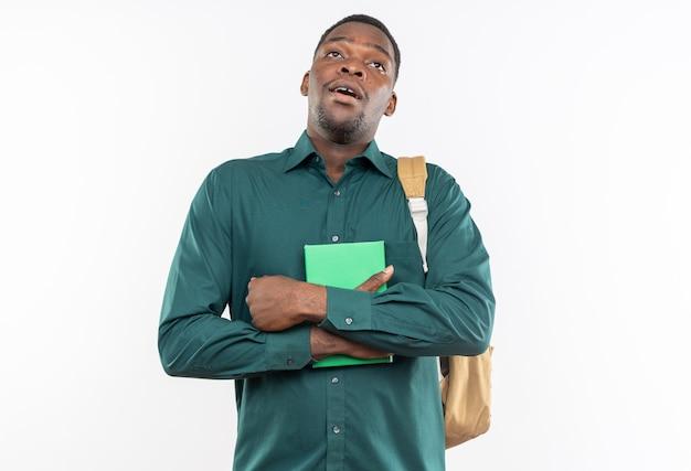 本を持って、コピースペースのある白い壁に孤立して見上げるバックパックで驚いた若いアフリカ系アメリカ人の学生