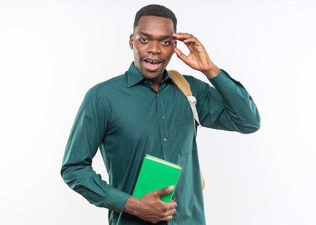 Giovane studente afroamericano sorpreso con lo zaino che tiene il libro e che gli mette la mano sulla fronte