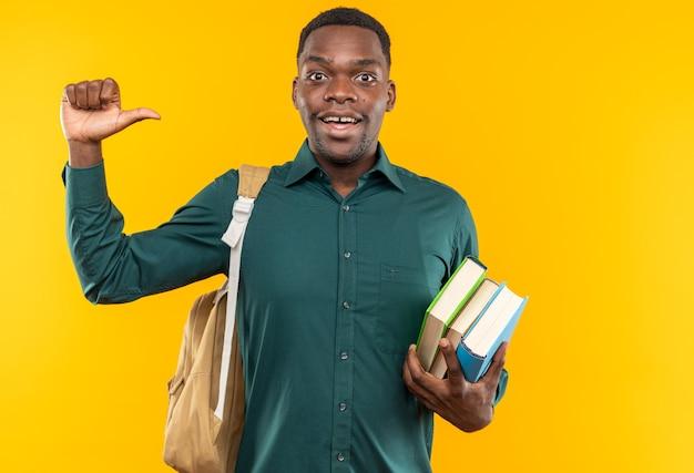 책을 들고 옆을 가리키는 배낭을 메고 놀란 젊은 아프리카계 미국인 학생