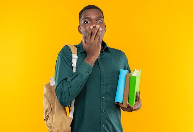 Giovane studente afroamericano sorpreso con lo zaino che tiene libri e si mette la mano sulla bocca