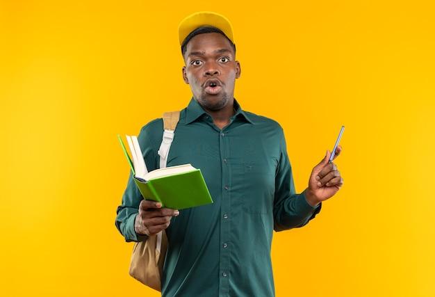 책과 펜을 들고 모자와 배낭을 가진 놀란 젊은 아프리카계 미국인 학생