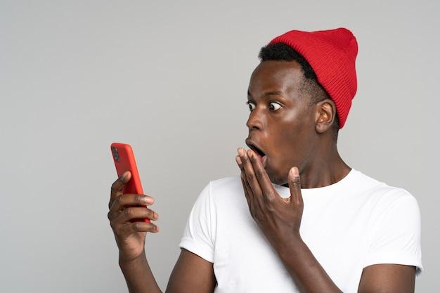놀란 젊은 아프리카 남자는 큰 눈을 뜨고 손으로 입을 덮고 전례없는 저렴한 가격, 알림 또는 메시지로 충격을 받고 휴대 전화를보고 스튜디오 회색 배경에 고립되었습니다.