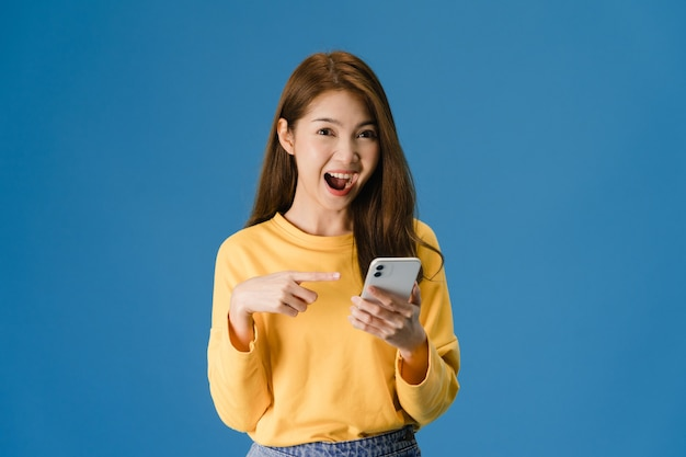 Surprised young asia lady using mobile phone with positive expression, smiles broadly, dressed in casual clothing and looking at camera on blue background. happy adorable glad woman rejoices success.