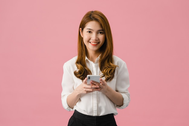 Surprised young asia lady using mobile phone with positive expression, smiles broadly, dressed in casual clothing and looking at camera on pink background.